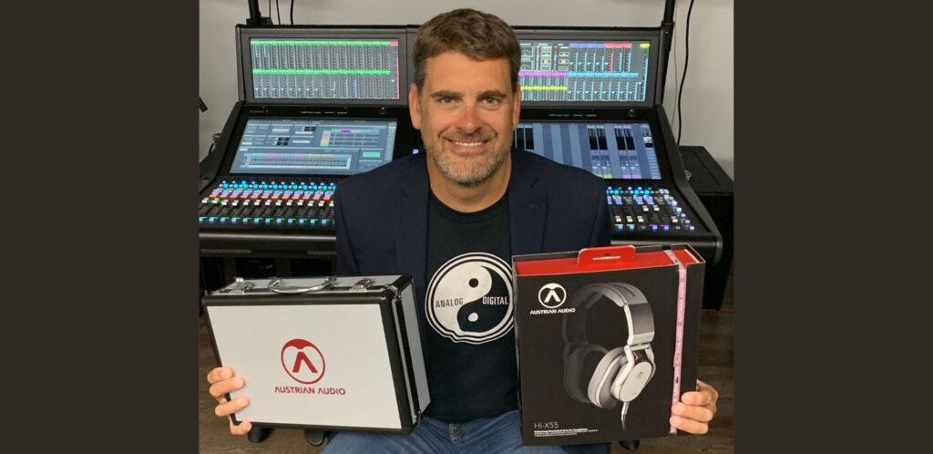 Bryan Bradley President of Group One holds HiX-55 headphones.
